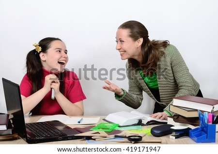 Female teacher and schoolgirl teenager at a school desk socialize animatedly, are laughing, smiling.