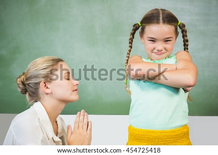 Female teacher apologizing girl in the classroom at school - stock photo
