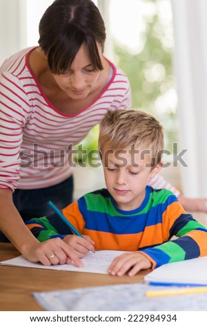 Female teacher assisting a young boy at school standing over him pointing at something he has written in his notebook - stock photo