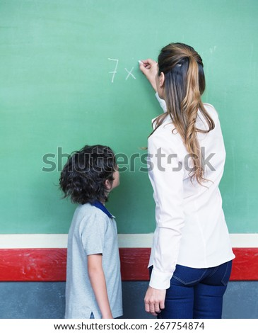 Female teacher explaining math to primary school kid. - stock photo