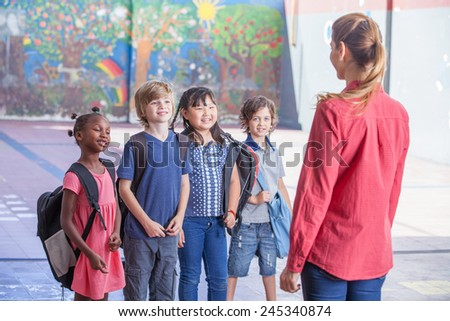 Female teacher explaining to multirace students in schoolyard. - stock photo