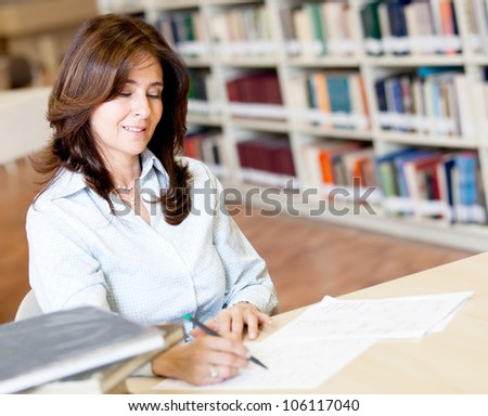 Female teacher grading exams at the library - stock photo