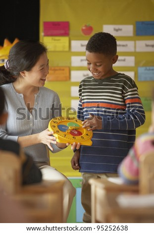 Female teacher helping student to tell time - stock photo