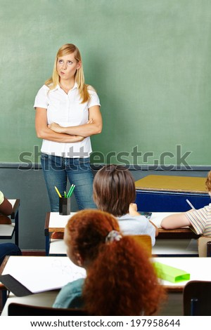 Female teacher in elementary school class thinking in front of chalkboard