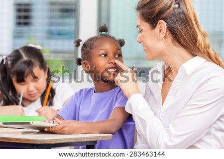 Female teacher joking with her african girl pupil.