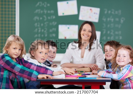 Female teacher leading a class activity with a group of her young schoolchildren all seated together around a table as she smiles happily at the camera with a chalkboard background
