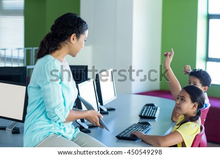 Female teacher looking at children raising hands while holding digital tablet in computer class - stock photo