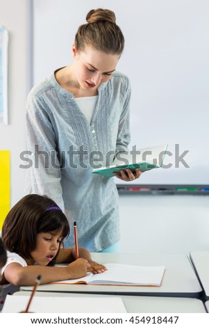 Female teacher looking at students writing on book in classroom
