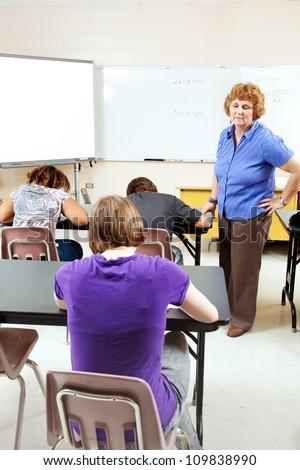 Female teacher monitoring a test in high school setting. - stock photo