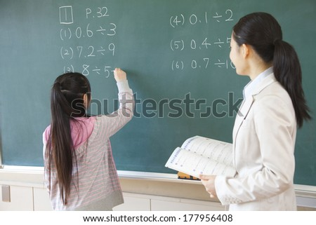 Female teacher standing next to the elementary Japanese girl who solves the problem of blackboard