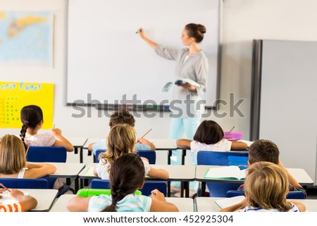 Female teacher teaching schoolchildren in classroom