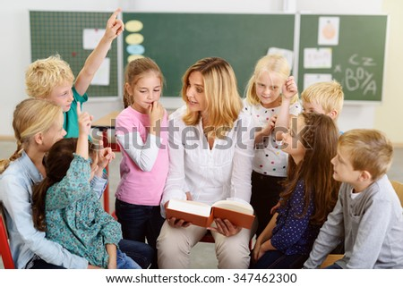 Female Teacher Teaching Something to her Kindergarten Students About the Story in the Book Inside the Classroom. - stock photo