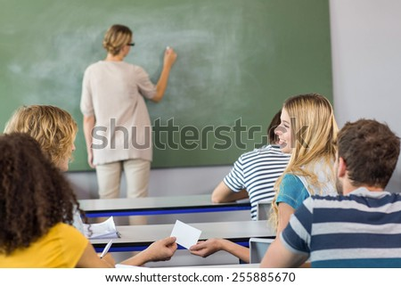 Female teacher teaching students in the class