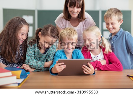 Female teacher with a diverse group of young pupils in class all smiling as they cluster around a tablet computer held by a young boy in the centre