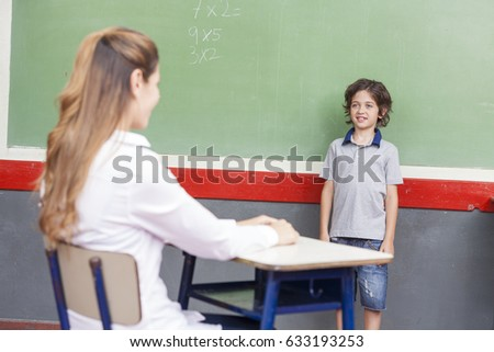 Female teacher with caucasian child at chalkboard. School concept.
