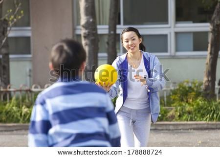 Female teachers and elementary Japanese boy playing dodge ball - stock photo