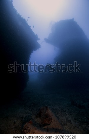 Female technical divers exploring the underwater shipwreck Eagle in the Florida Keys off of Islamorada just south of Key Largo. Swimming in between the split from the bow to the main body. - stock photo
