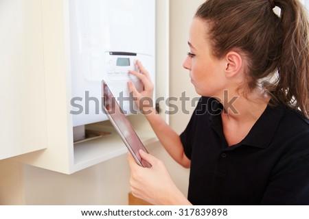 Female technician servicing a boilerusing tablet computer - stock photo