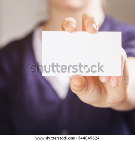 female teen girl hold business paper card closeup, toned photo