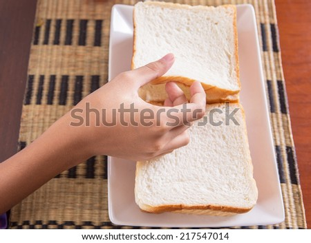 Female teen hand picking up piece of bread