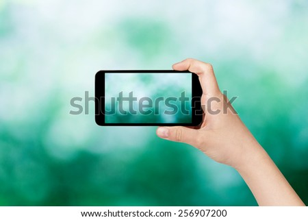 female teen hand taking picture with smart phone of green - stock photo