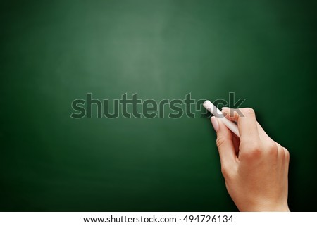Female teen hand to draw something on blackboard with chalk