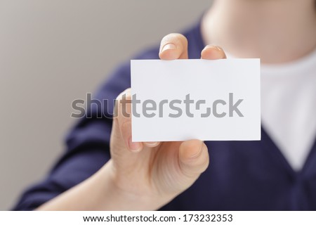 female teen holding empty business card in front of camera, blurred background