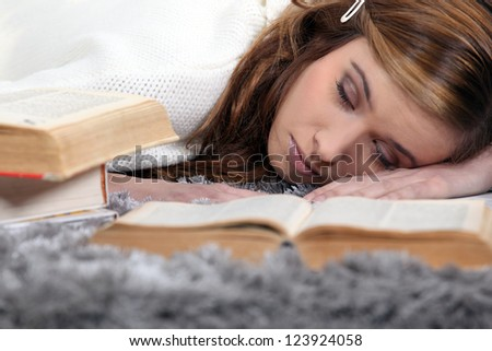 Female teenager asleep on a book - stock photo
