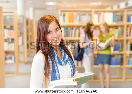 Female teenager student standing and reading book at high-school library - stock photo