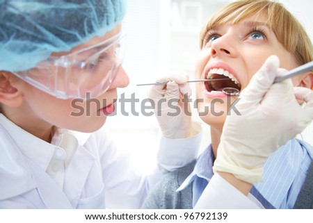 Female teeth being checked by doctor - stock photo
