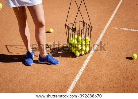 female tennis player collects tennis balls on a basket