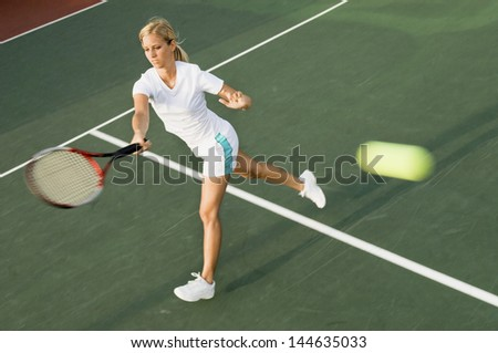 Female tennis player hitting tennis ball with forehand on court
