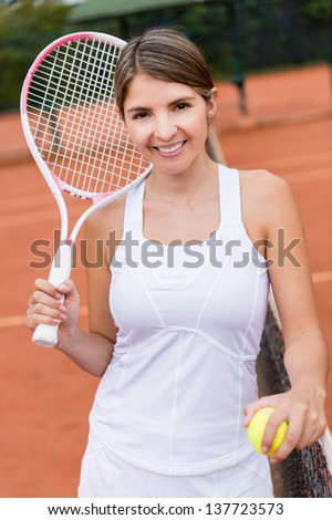 Female tennis player looking happy at the court