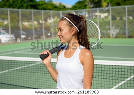 Female tennis player portrait with tennis racket outdoors in tennis court in summer. Fit female athlete playing tennis living healthy active sport and fitness lifestyle. Mixed race Asian Caucasian. - stock photo