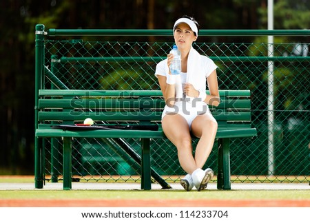 Female tennis player rests with bottle of water on the bench at the tennis court - stock photo