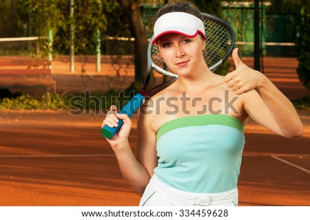 Female tennis player showing like or thumb-up gesture and holding racket on shoulder - stock photo