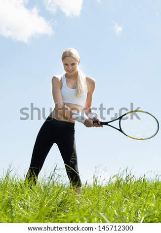 Female Tennis Player Standing In Field Holding Racquet And Ball