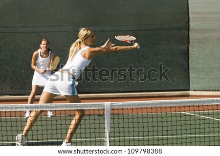 Female tennis player stretching for a shot with partner standing in background