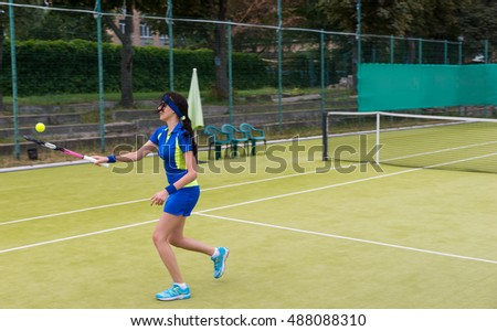 Female tennis player wearing a sportswear warming up before tennis match on a court outdoor in summer or spring