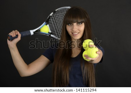 Female tennis player with racket and ball on black background - stock photo