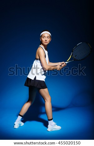 Female tennis-player with racket ready to hit a tennis ball. - stock photo