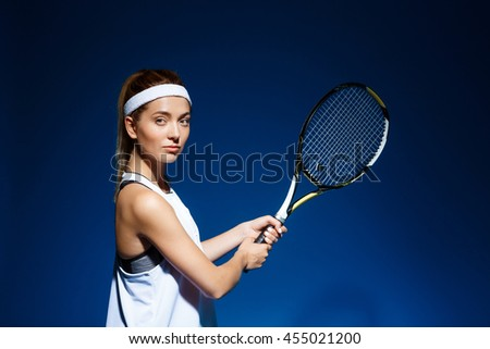 Female tennis player with racket ready to hit a tennis ball. - stock photo