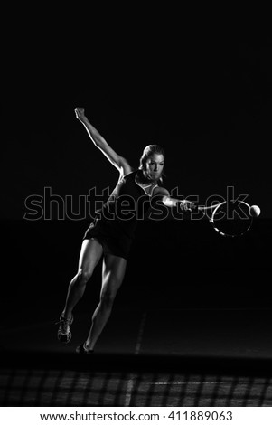 Female Tennis Player With Racket Ready To Hit A Tennis Ball - Isolated On Black