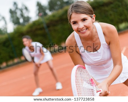Female tennis players playing doubles and looking happy - stock photo