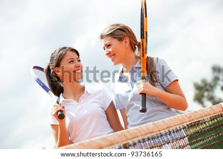 Female tennis players talking at a clay court - stock photo