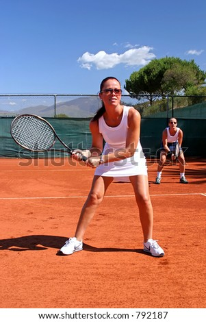 Female tennis players waiting for service on red asphalt court in the sun with blue sky in Spain - stock photo
