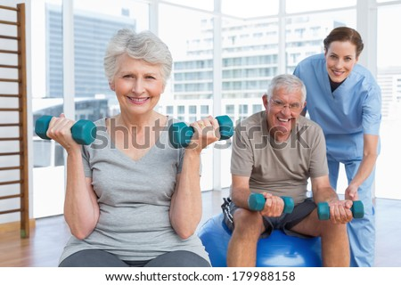 Female therapist assisting senior couple with dumbbells in the medical office - stock photo