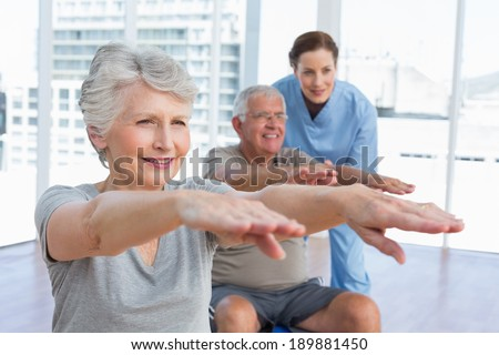 Female therapist assisting senior couple with exercises in the medical office - stock photo