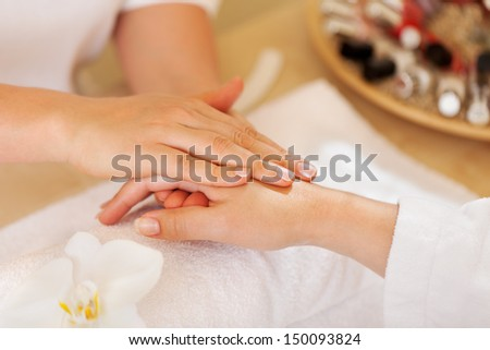 female therapist giving a hand massage to woman - stock photo
