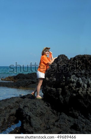 Female tourist climbs and explores the lava rock beaches on Anaehoomalu Bay on the Kohala Coast of the Big Island.  She is wearing an orange tee shirt and straw hat with polka dotted scarf. - stock photo